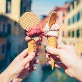 Mains tenant la crème glacée dans le cône de gaufre photographie stock libre de droits