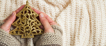 Mains tenant la décoration d'or d'arbre de scintillement de Noël Photos stock