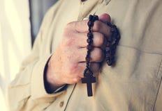 Mains tenant la foi croisée de prière dans la religion de christianisme images libres de droits