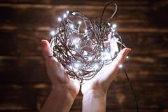 Mains tenant la guirlande de Noël image stock