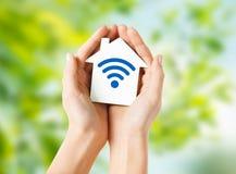 Mains tenant la maison avec l'icône de signal d'onde radio images libres de droits