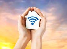 Mains tenant la maison avec l'icône de signal d'onde radio photographie stock