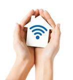 Mains tenant la maison avec l'icône de signal d'onde radio Photographie stock libre de droits