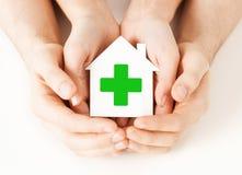 Mains tenant la maison de papier avec la croix verte Image stock