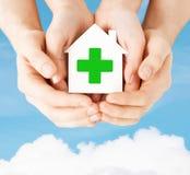 Mains tenant la maison de papier avec la croix verte Photo stock