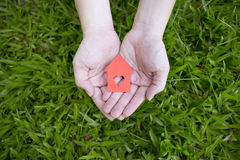 Mains tenant la maison de papier rouge Image stock