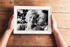 Mains tenant la photo noire et blanche des couples supérieurs dans la photo Photos stock