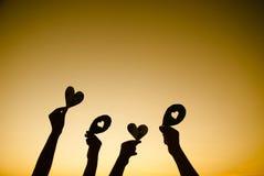 Mains tenant la silhouette de coeurs sur le fond de lever de soleil Photographie stock libre de droits