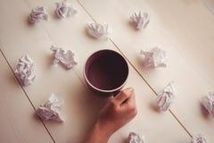 Mains tenant la tasse de café à côté des boules de papier Photo stock