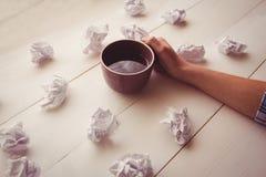 Mains tenant la tasse de café à côté des boules de papier Photos stock