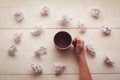 Mains tenant la tasse de café à côté des boules de papier Photographie stock libre de droits