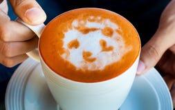 Mains tenant la tasse de café, thé chaud de lait Image stock
