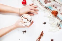 Mains tenant la tasse de chocolat chaud avec la guimauve Image libre de droits