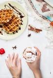 Mains tenant la tasse de chocolat chaud avec la guimauve, gaufre belge Image libre de droits