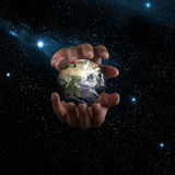 Mains tenant la terre images stock