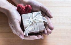 Mains tenant le boîte-cadeau et la soie en forme de coeur rouge Images stock