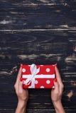 Mains tenant le boîte-cadeau mignon de point de polka Image libre de droits