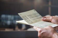 Mains tenant le carnet bancaire d'économie, banque de livre sur un bureau de banque Photographie stock