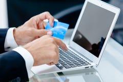Mains tenant le chariot de crédit par un clavier d'ordinateur portable Photos libres de droits