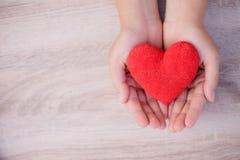 mains tenant le coeur rouge fait main sur le fond en bois Image stock