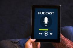 Mains tenant le comprimé avec le concept de podcast sur l'écran Photographie stock