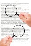 Mains tenant le document de lecture de loupe Image libre de droits