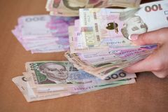 Mains tenant le hryvnia ukrainien d'argent La devise nationale photographie stock libre de droits
