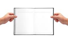Mains tenant le livre Images stock