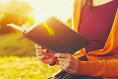 Mains tenant le livre et la lecture Images stock