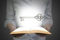 Mains tenant le livre ouvert avec la clé de trésor Images libres de droits