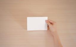 Mains tenant le livret blanc vide de brochure dans la main feuillet photos libres de droits