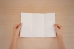 Mains tenant le livret blanc vide de brochure dans la main feuillet image libre de droits