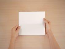 Mains tenant le livret blanc vide de brochure dans la main feuillet photo libre de droits