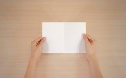 Mains tenant le livret blanc vide de brochure dans la main feuillet photos stock
