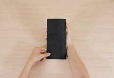 Mains tenant le livret noir vide de brochure dans la main feuillet photo stock