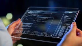 Mains tenant le PC de comprimé avec le codage sur l'écran clips vidéos