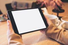 Mains tenant le PC noir de comprimé avec l'écran blanc vide avec des tasses de café sur la table en bois en café moderne Photographie stock libre de droits