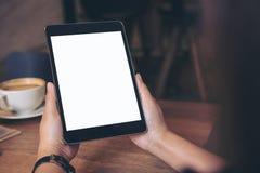 Mains tenant le PC noir de comprimé avec l'écran blanc vide avec la tasse et le téléphone portable de café sur la table en bois e Photographie stock libre de droits