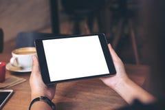 Mains tenant le PC noir de comprimé avec l'écran blanc vide avec la tasse et le téléphone portable de café sur la table en bois e Photos stock