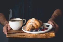 Mains tenant le plateau en bois avec le croissant de petit déjeuner continental et la tasse de café Photographie stock