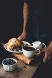 Mains tenant le plateau en bois avec le croissant, le café, la crème et les fruits de petit déjeuner continental Image libre de droits