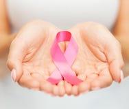 Mains tenant le ruban rose de conscience de cancer du sein Image libre de droits
