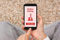 Mains tenant le smartphone avec la moquerie en ligne d'application de datation  Image libre de droits