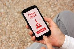 Mains tenant le smartphone avec la moquerie en ligne d'application de datation  Images libres de droits