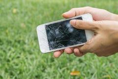 Mains tenant le smartphone mobile cassé Images stock