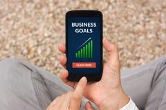 Mains tenant le téléphone intelligent avec le concept de buts d'affaires sur l'écran Photographie stock