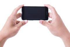 Mains tenant le téléphone intelligent mobile avec l'écran vide d'isolement sur W Image libre de droits