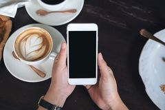 Mains tenant le téléphone portable blanc avec l'écran noir vide avec des tasses de café sur la table en bois dans le restaurant Photographie stock