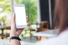 Mains tenant le téléphone portable blanc avec l'écran blanc vide en café moderne Image stock