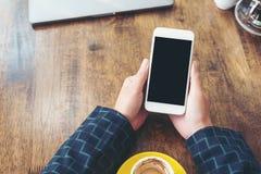 Mains tenant le téléphone portable blanc avec la tasse de bureau noire vide d'écran et de café sur la table en bois à l'arrière-p Photos libres de droits